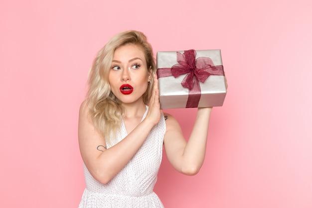 Eine junge schöne dame der vorderansicht im weißen kleid, die geschenkbox hält