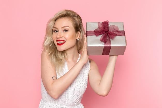Eine junge schöne dame der vorderansicht im weißen kleid, die geschenkbox mit lächeln auf ihrem gesicht hält