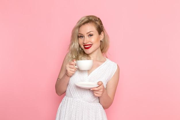Eine junge schöne dame der vorderansicht im weißen kleid, die tasse tee mit lächeln auf ihrem gesicht hält