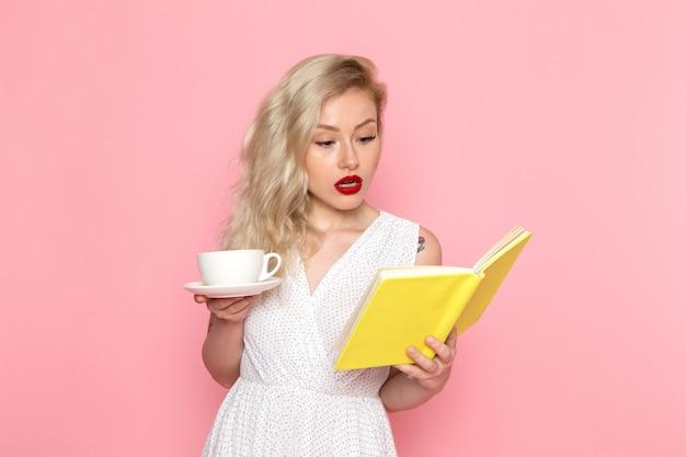 Eine junge schöne dame der vorderansicht im weißen kleid trinkt einen tee, der ein heft liest