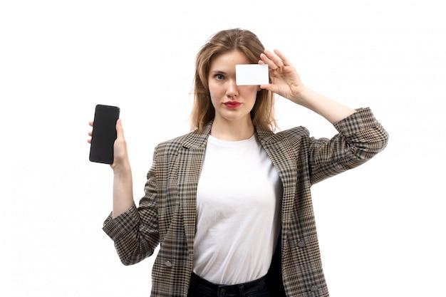 Eine junge schöne dame der vorderansicht in den schwarzen jeans und im mantel des weißen t-shirts, die schwarzes smartphone und weiße karte auf dem weiß halten