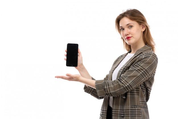 Eine junge schöne dame der vorderansicht in den schwarzen jeans und im mantel des weißen t-shirts, die smartphone auf dem weiß zeigt