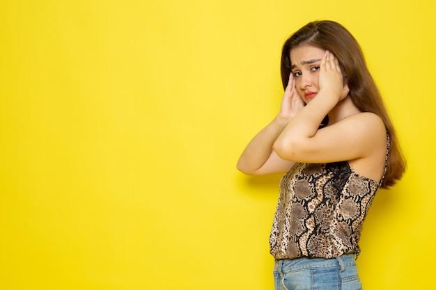 Eine junge schöne dame der vorderansicht in der braunen bluse und in den blauen jeans, die kopfschmerzen haben