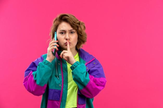 Eine junge schöne dame der vorderansicht in der bunten jacke der schwarzen hose des säurefarbenen hemdes, die am telefon spricht, das am telefon spricht