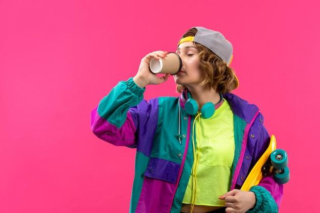 Eine junge schöne dame der vorderansicht in der bunten jacke der schwarzen hose des säurefarbenen hemdes mit blauen kopfhörern, die skateboard halten kaffee trinken