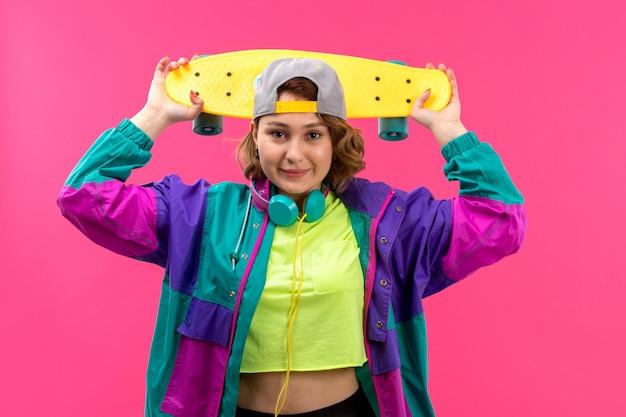Eine junge schöne dame der vorderansicht in der bunten jacke der schwarzen hose des säurefarbenen hemdes mit blauen kopfhörern, die skateboard halten