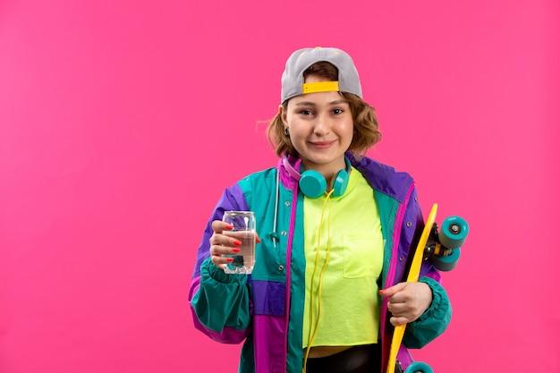 Eine junge schöne dame der vorderansicht in der bunten jacke der schwarzen hose des säurefarbenen hemdes mit blauen kopfhörern, die skateboardglas halten