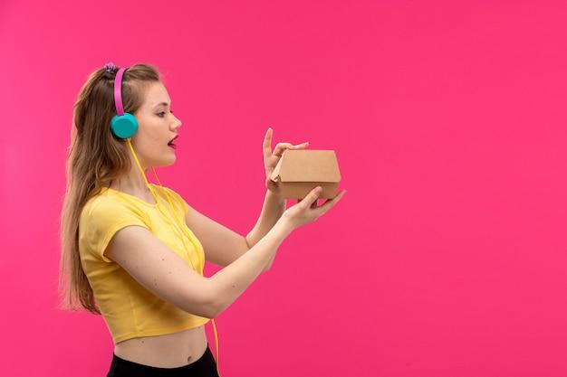 Eine junge schöne dame der vorderansicht in der schwarzen hose des orangefarbenen hemdes lächelnd, die musik hört, die paketbox hält
