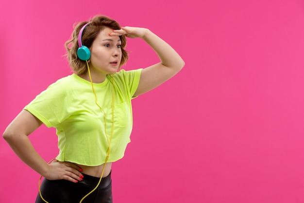 Eine junge schöne dame der vorderansicht in der schwarzen hose des säurefarbenen hemdes mit blauen kopfhörern, die musik hören, die in die ferne starrt
