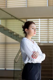 Eine junge schöne dame der vorderansicht in der schwarzen hose des weißen hemdes, die die entfernung in der halle betrachtet, die während der tagesaufbaujobaktivität wartet