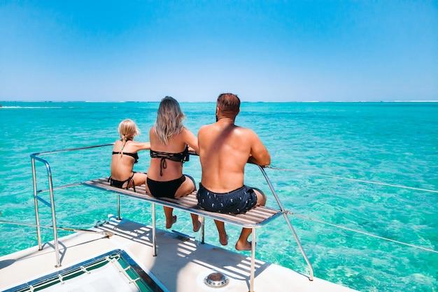 Eine junge schöne familie mit einem kind sieht auf einer yacht am korallenriff der insel mauritius sitzen. reisen und erholung auf der insel mauritius