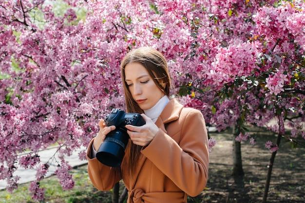 Eine junge schöne fotografin geht und fotografiert gegen einen blühenden apfelbaum. hobbys, erholung.