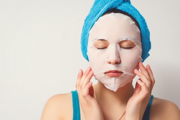 Eine junge schöne frau benutzt eine feuchtigkeitsspendende gesichtsmaske aus kosmetischem stoff mit einem handtuch um den kopf. auf weißer wand.