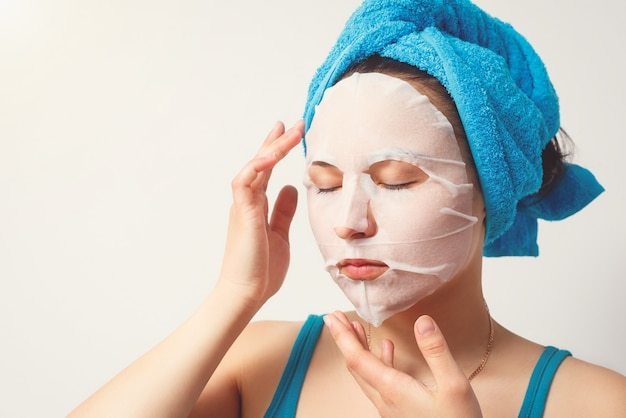 Eine junge schöne frau benutzt eine feuchtigkeitsspendende gesichtsmaske aus kosmetischem stoff mit einem handtuch um den kopf.