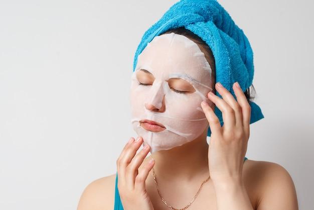 Eine junge schöne frau benutzt eine feuchtigkeitsspendende gesichtsmaske aus kosmetischem stoff mit einem handtuch