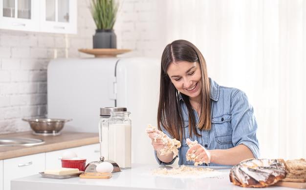 Eine junge schöne frau bereitet hausgemachte kuchen in der küche zu