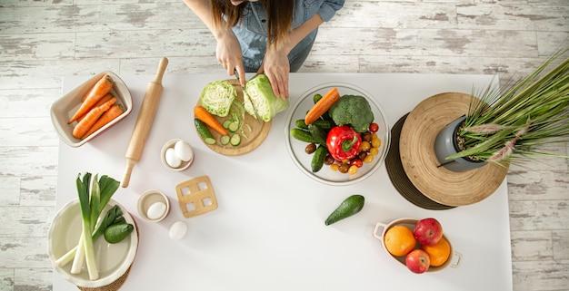 Eine junge schöne frau bereitet in der küche einen salat mit verschiedenen gemüsesorten zu.