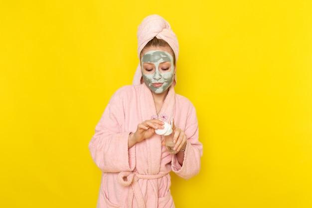 Eine junge schöne frau der vorderansicht im rosa bademantel, der baumwolle hält