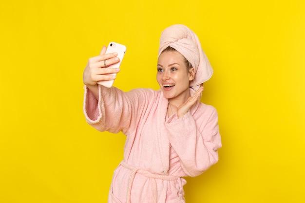 Eine junge schöne frau der vorderansicht im rosa bademantel, der ein foto macht
