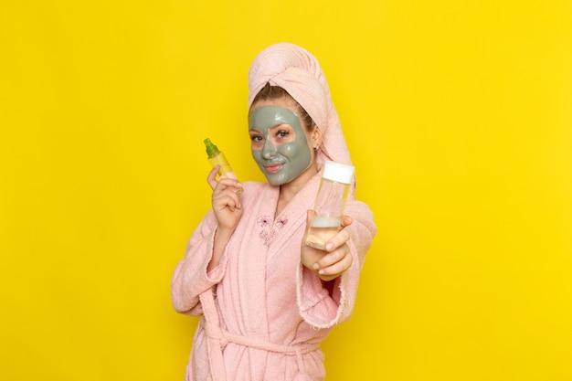 Eine junge schöne frau der vorderansicht im rosa bademantel, der flaschensprays mit lächeln hält