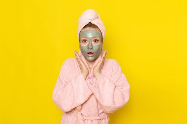 Eine junge schöne frau der vorderansicht im rosa bademantel, der gerade mit überraschtem ausdruck aufwirft