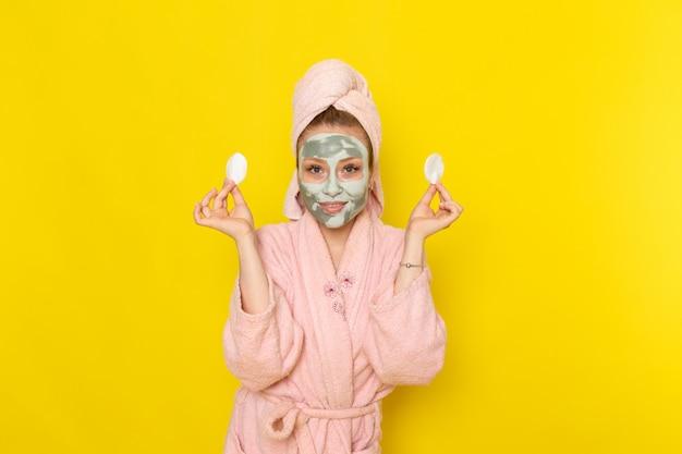 Eine junge schöne frau der vorderansicht im rosa bademantel, der kleine baumwollstoffe hält