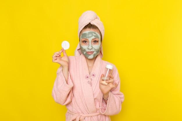 Eine junge schöne frau der vorderansicht im rosa bademantel, der make-up-reinigerspray hält