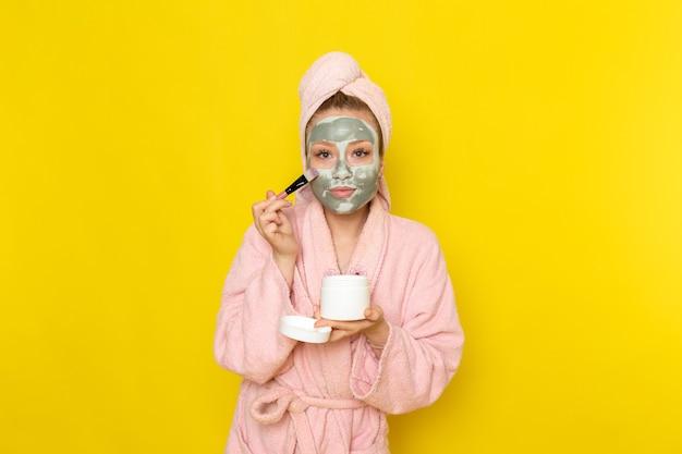 Eine junge schöne frau der vorderansicht im rosa bademantel, der make-up tut
