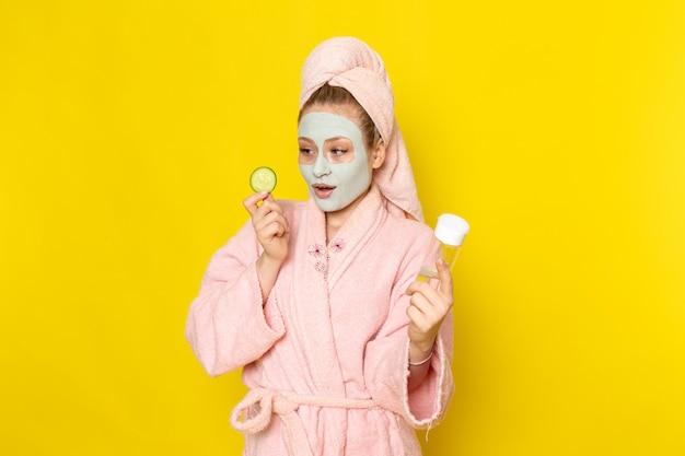 Eine junge schöne frau der vorderansicht im rosa bademantel, der spray und gurke hält