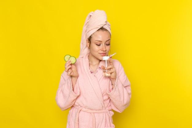 Eine junge schöne frau der vorderansicht im rosa bademantel, der spray und gurkenrunden hält