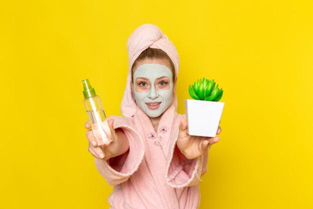 Eine junge schöne frau der vorderansicht im rosa bademantel, der spray und kleine grüne pflanze hält
