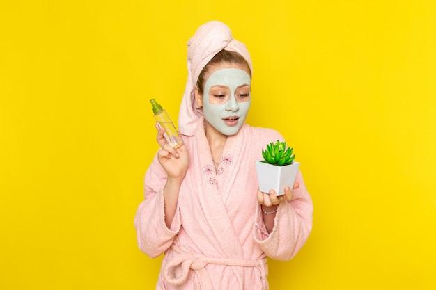 Eine junge schöne frau der vorderansicht im rosa bademantel, der spray und kleine pflanze hält