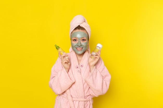 Eine junge schöne frau der vorderansicht im rosa bademantel, der sprays mit lächeln hält