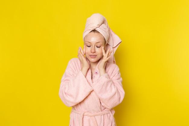 Eine junge schöne frau der vorderansicht im rosa bademantel, die ihr gesicht mit creme reibt
