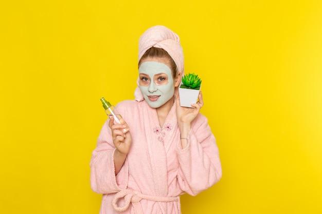 Eine junge schöne frau der vorderansicht im rosa bademantel, die make-up-reinigerspray und kleine pflanze hält