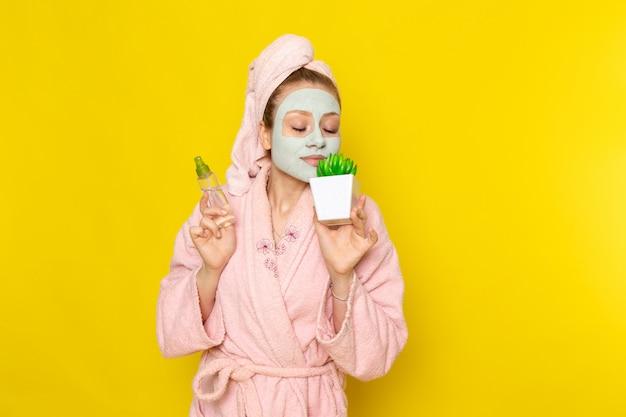 Eine junge schöne frau der vorderansicht im rosa bademantel, die sprühflasche und grüne pflanze auf dem gelben hintergrund hält