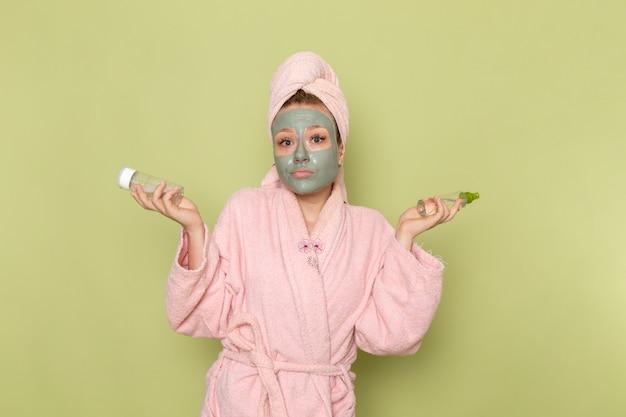 Eine junge schöne frau der vorderansicht im rosa bademantel mit gesichtsmaske, die sprays hält