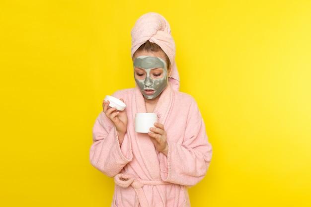 Eine junge schöne frau der vorderansicht im rosa bademantel mit gesichtsmaske, die weiße creme hält