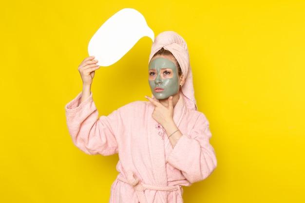 Eine junge schöne frau der vorderansicht im rosa bademantel mit gesichtsmaske, die weißes zeichen denken hält