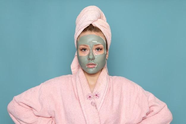 Eine junge schöne frau der vorderansicht im rosa bademantel mit gesichtsmaske