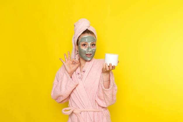 Eine junge schöne frau der vorderansicht im rosa bademantel mit gesichtsmaskenhaltecreme