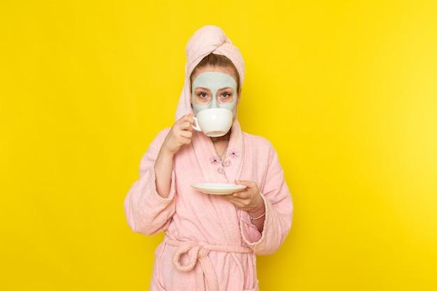 Eine junge schöne frau der vorderansicht im rosa bademantel mit maske, die heißen tee trinkt