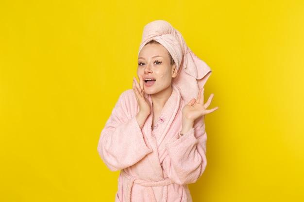 Eine junge schöne frau der vorderansicht im rosa bademantel unter verwendung der gesichtscreme