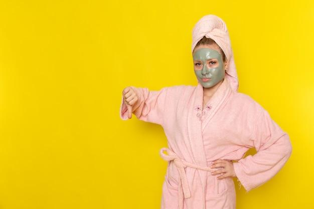 Eine junge schöne frau der vorderansicht im rosa bademantel zeigt unähnliches zeichen