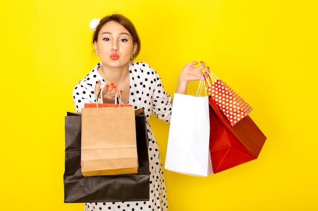 Eine junge schöne frau der vorderansicht im schwarzweiss-tupfenkleid, das einkaufspakete auf gelb hält