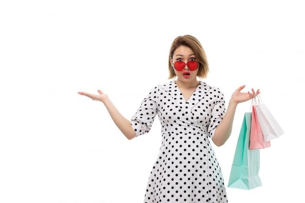 Eine junge schöne frau der vorderansicht im schwarzweiss-tupfenkleid in der roten sonnenbrille, die einkaufspakete hält, die überraschten ausdruck aufwerfen