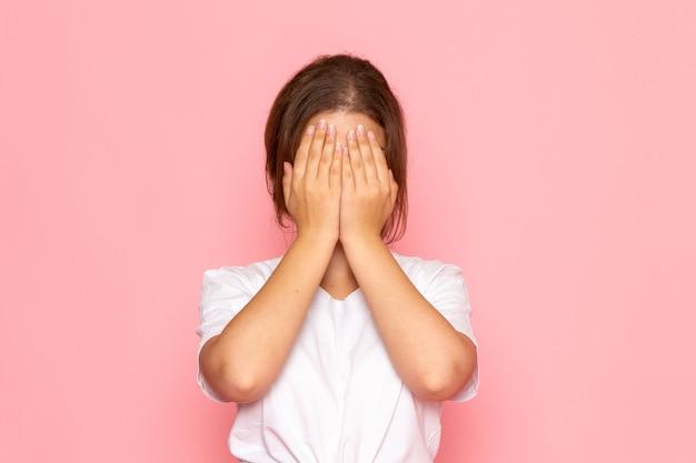 Eine junge schöne frau der vorderansicht im weißen hemd, das ihr gesicht bedeckt