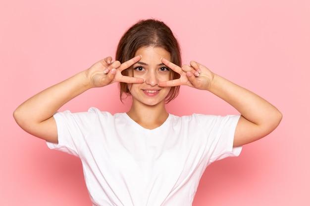 Eine junge schöne frau der vorderansicht im weißen hemd, das mit den fingern um ihre augen aufwirft und lächelt