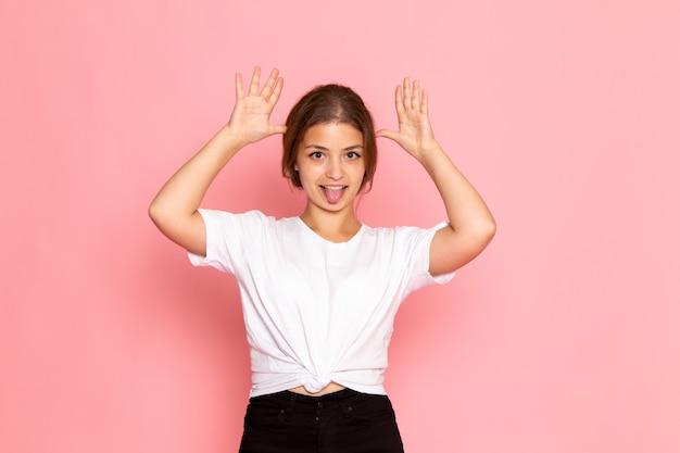 Eine junge schöne frau der vorderansicht im weißen hemd mit dem aufstellen mit lustigen gesten