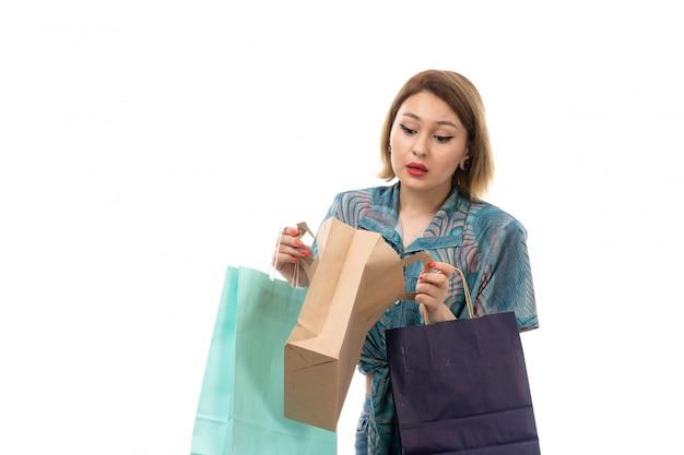 Eine junge schöne frau der vorderansicht in den blauen jeans der bluse, die einkaufspakete halten